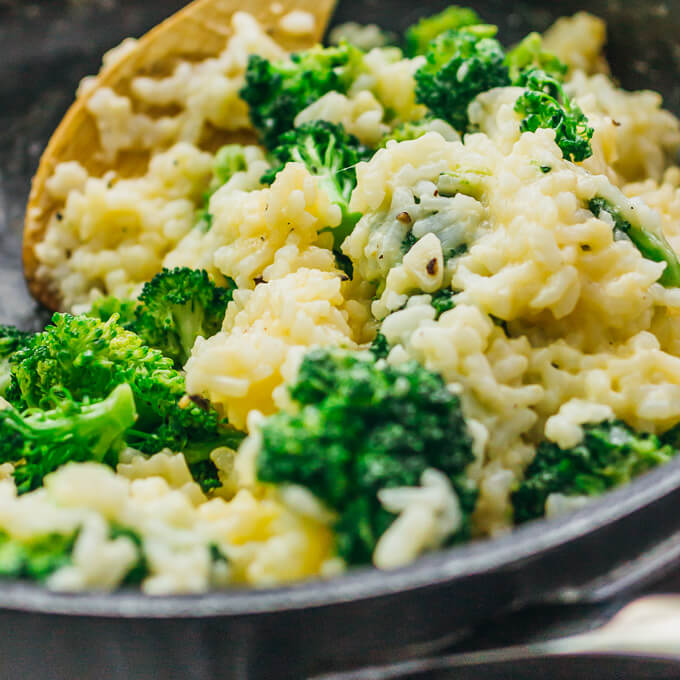Closeup side view of broccoli cheddar risotto in a black skillet