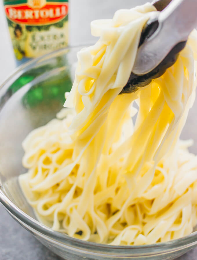 Tossing fettuccine pasta with olive oil