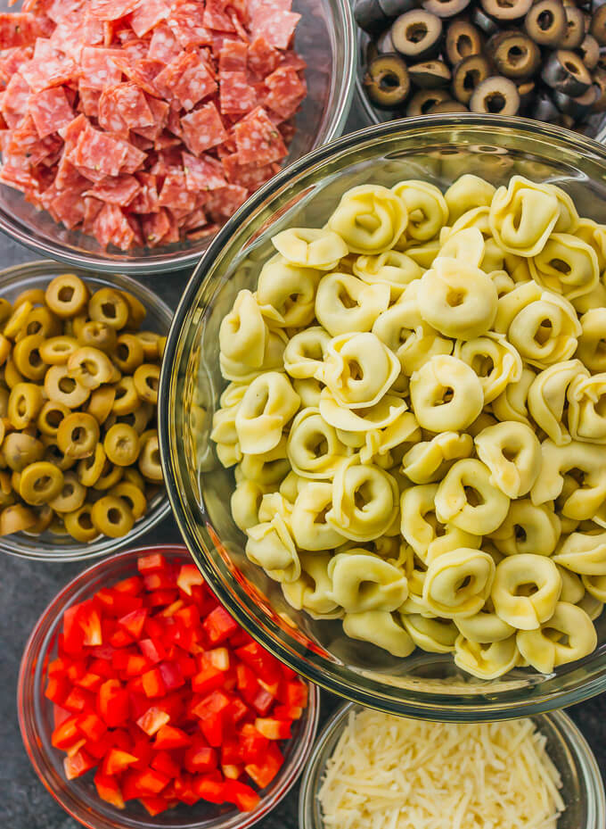 Ingredients for tortellini pasta salad including olives, salami, and cheese