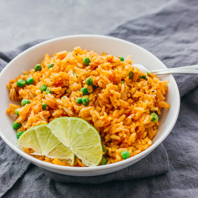 Serving easy Mexican rice with peas in a white bowl with lime wedges
