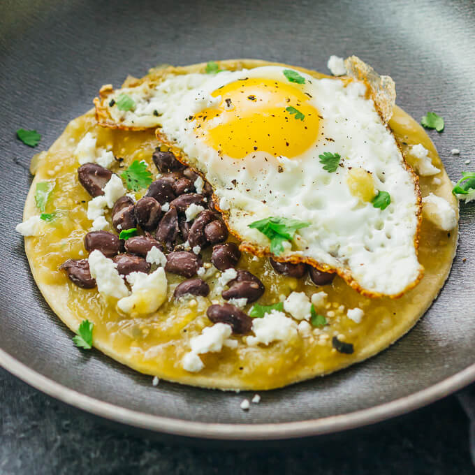 These healthy huevos rancheros are so easy and they make for a delicious breakfast; my favorite toppings include salsa verde, black beans, and crumbled Mexican cheese.