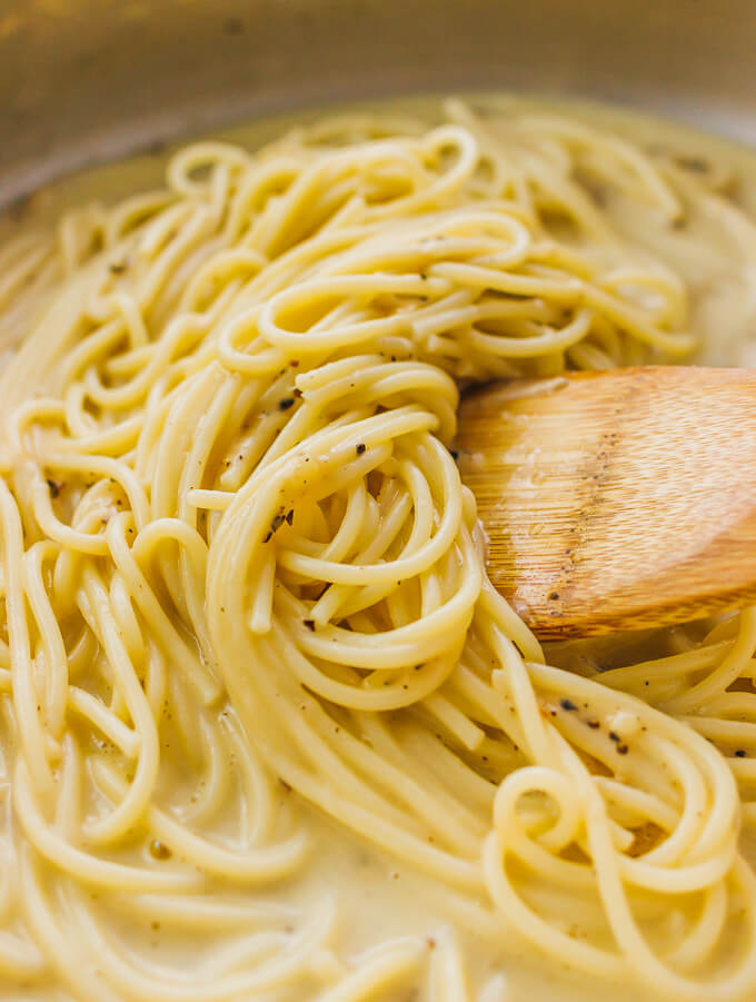 A wooden spoon stirring cacio e pepe pasta in a pan