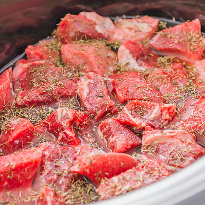 Beef stew meat topped with herbs in a slow cooker