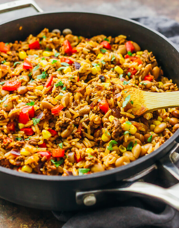 A Southwest skillet with ground beef, rice, peppers, onions, pinto beans, corn, and cayenne in a skillet
