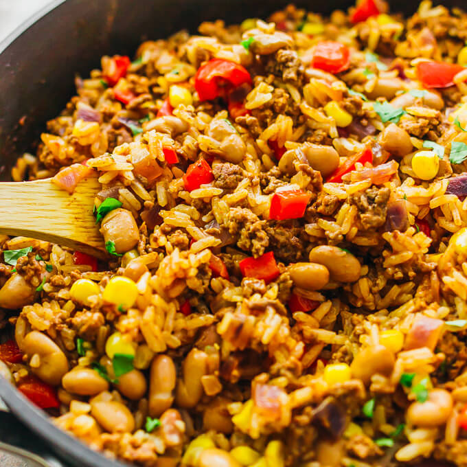 Stirring southwest skillet with beef, rice, beef, and beans