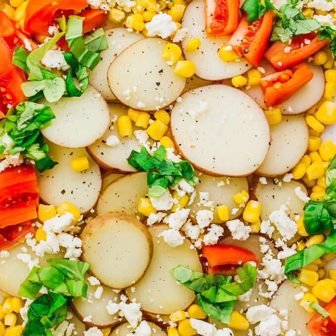 Drizzled with a balsamic horseradish dressing, this flavorful potato salad has sliced red potatoes, tomatoes, corn, feta cheese, and basil leaves.