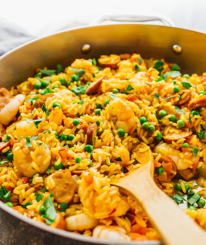 Shrimp paella with peas in a large silver saute pan