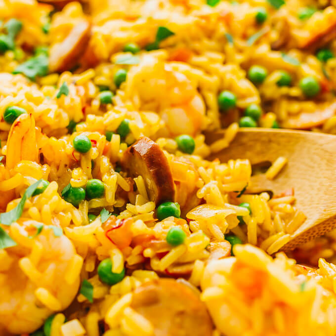Close up view of paella with shrimp, smoked sausage, tomatoes, onions, peas, garlic, and saffron