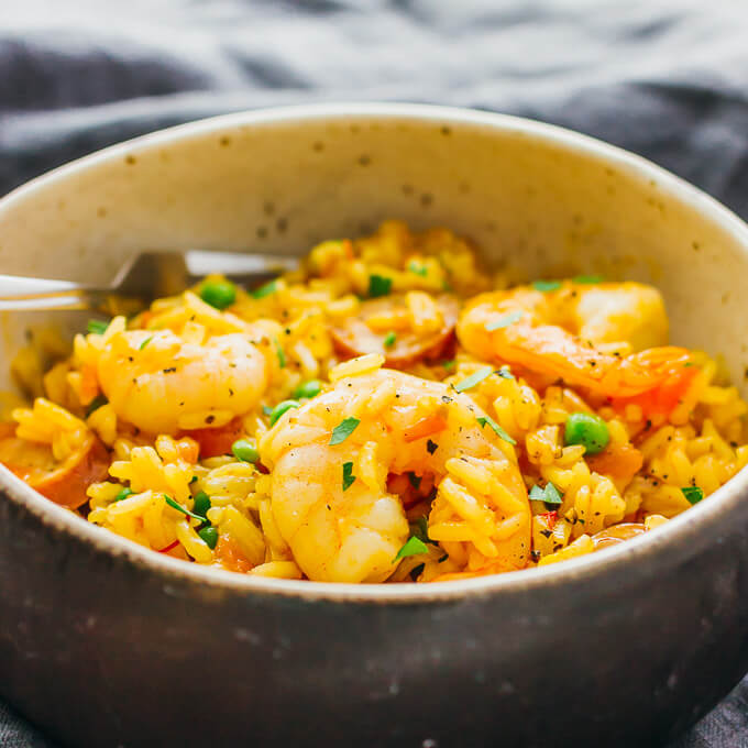 This is my everyday paella: an easy one pot meal with shrimp, smoked sausage, tomatoes, onions, peas, garlic, and saffron.