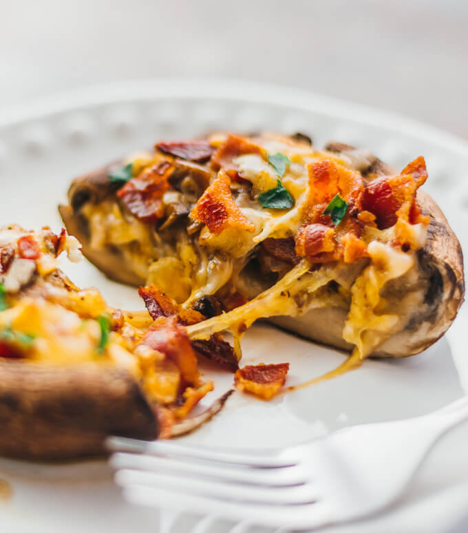 Stuffed portobello mushroom sliced in half and topped with bacon and cheddar cheese