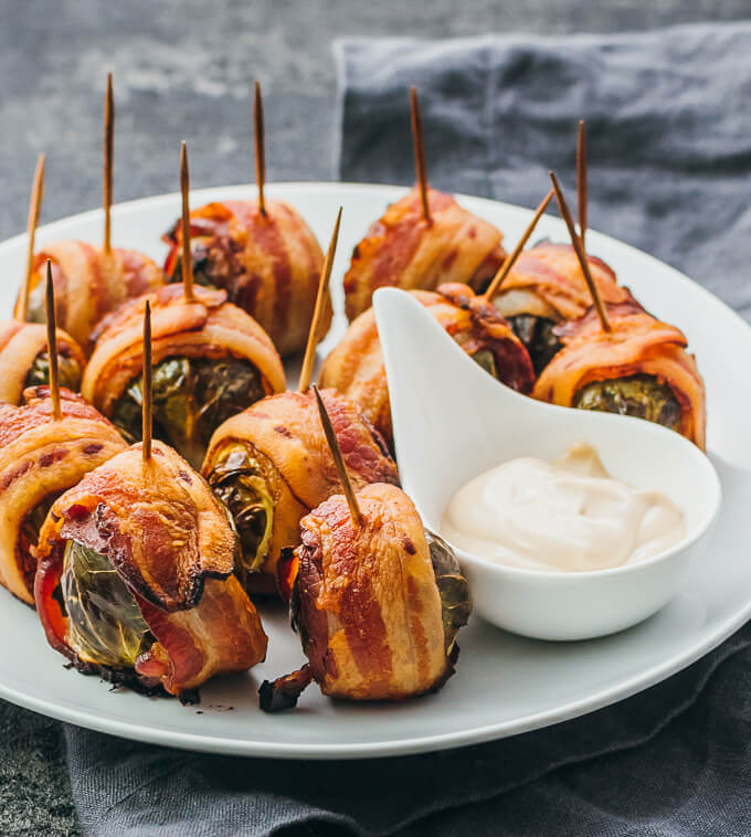 Roasted bacon wrapped brussels sprouts on a white plate served with a balsamic mayo dip