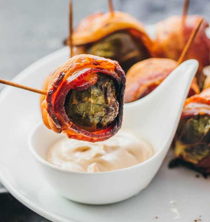 Single bacon wrapped brussels sprout being dipped into a balsamic mayo dipping sauce