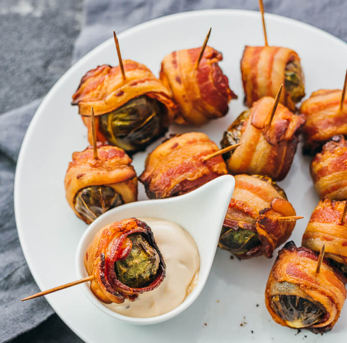 Delicious fall appetizer -- roasted brussels sprouts wrapped with crispy bacon slices -- served on toothpicks on a white plate