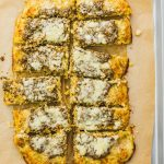 Make this healthy, low carb flatbread recipe using riced cauliflower. It's topped with pesto sauce and grated parmesan cheese.