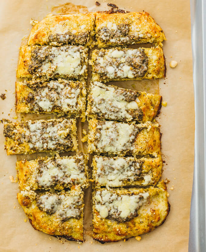 Cauliflower flatbread on brown parchment paper and cut up into slices
