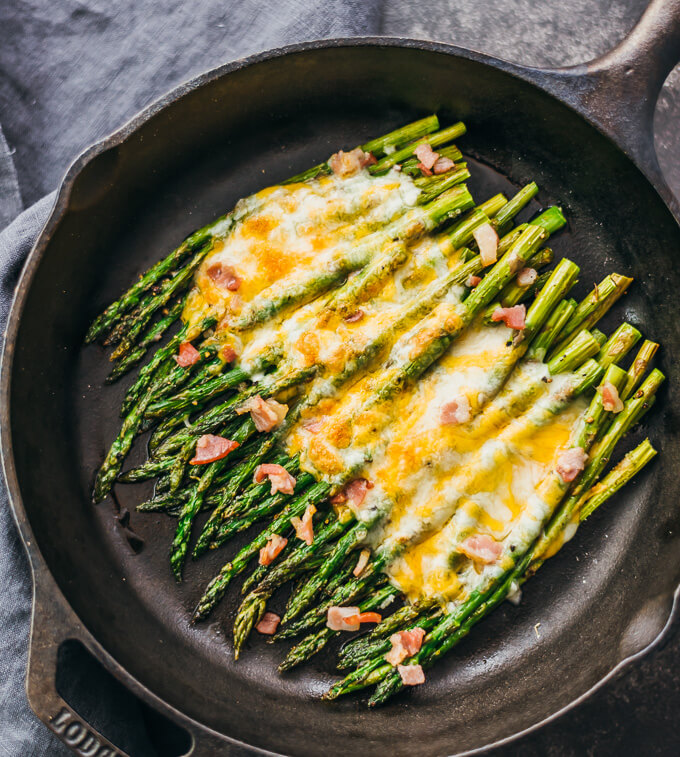 Baked asparagus side dish topped with melted cheese and bacon