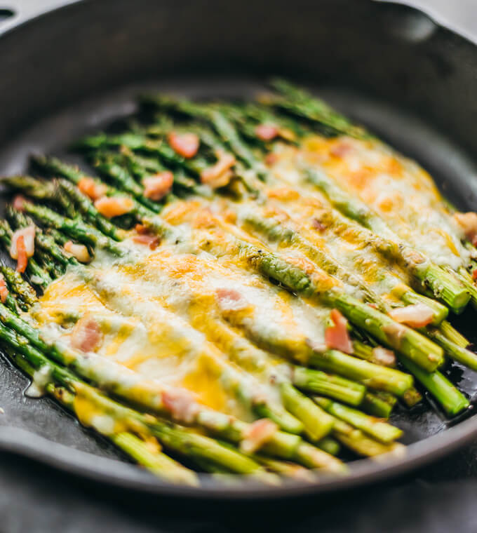 Baked asparagus in a cast iron pan with bacon and cheese