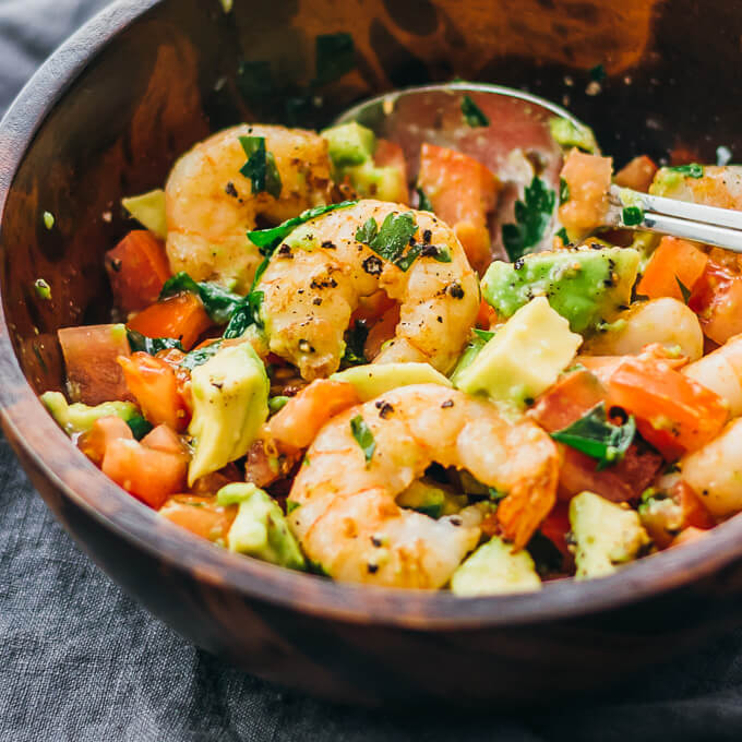 Here's a delicious and healthy cold shrimp salad with avocado, tomatoes, feta cheese, and lemon juice.