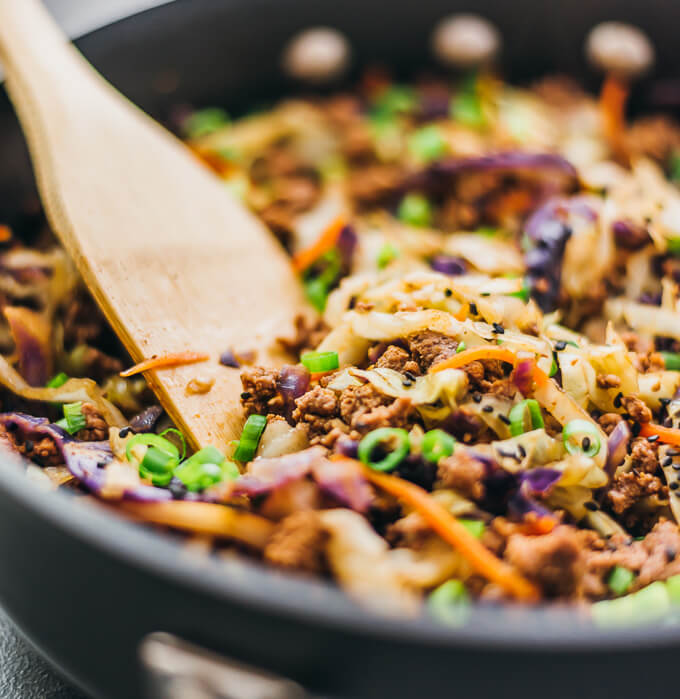 Close up view of stirring ground beef with cabbage in a pan using a wooden spoon