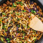 stirring cabbage and ground beef in skillet