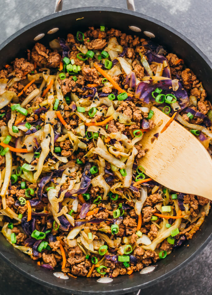 Overhead view making ground beef and cabbage stir fry in a black pan