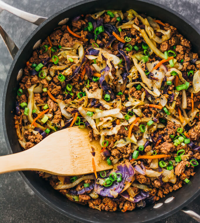 Cooking a fast and easy stir fry dinner with ground beef, cabbage, carrots, and scallions in a black pan
