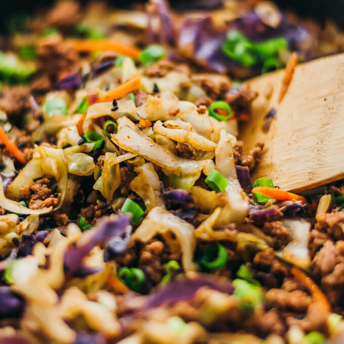 Scooping up cabbage and beef stir fry from a black pan
