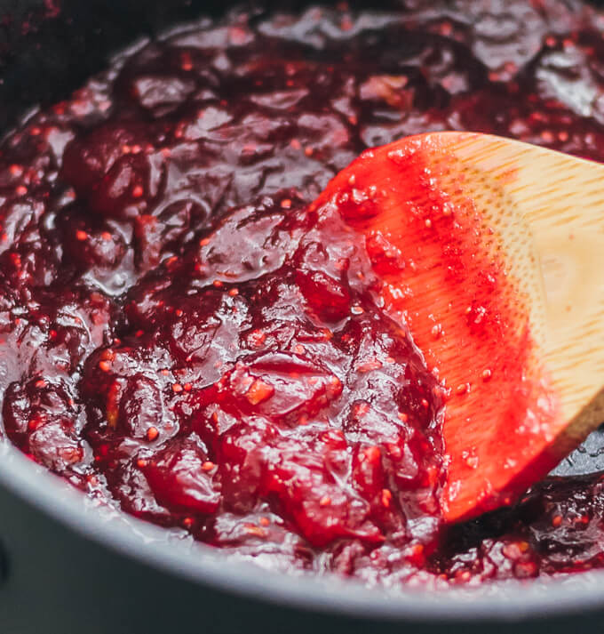 Stirring keto cranberry sauce with a wooden spoon in a black pot
