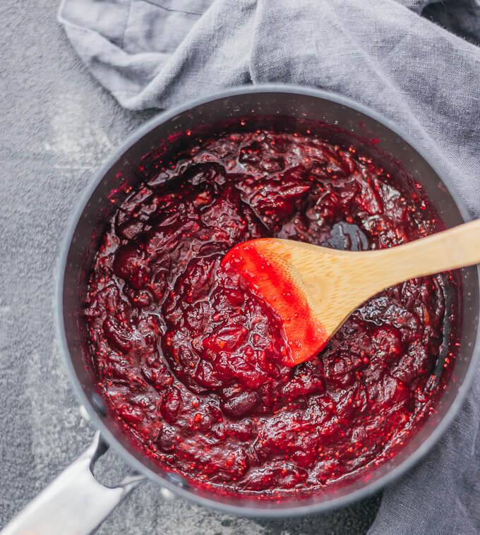 stirring cranberry sauce in saucepan