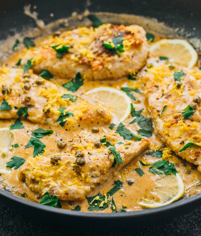 Lemon slices and parsley decorating chicken piccata with capers in a lemon butter cream sauce