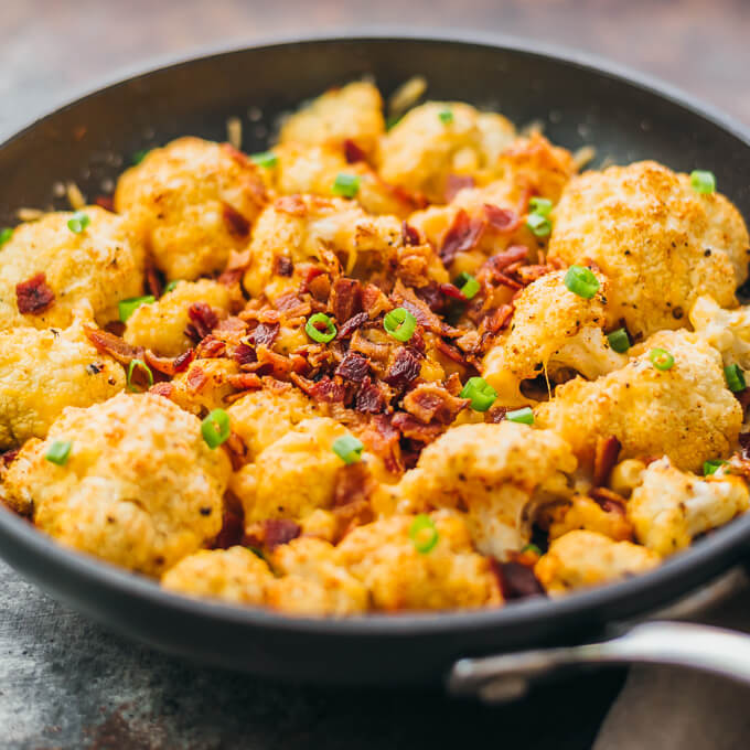 Easy roasted cauliflower with bacon and cheddar cheese in a black pan