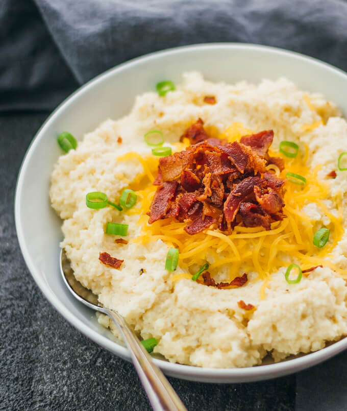 Mashed cauliflower served in a white bowl topped with scallions, crispy bacon, and cheddar cheese
