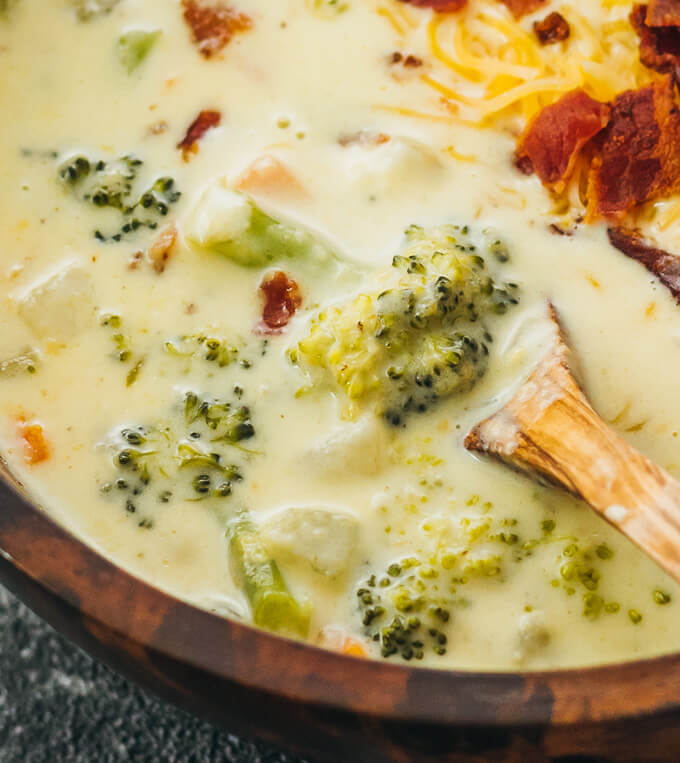 close up view of broccoli cheddar soup in wooden bowl