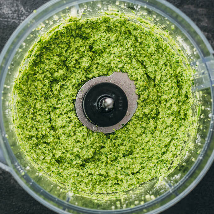 Freshly made pesto in a food processor bowl after pureeing