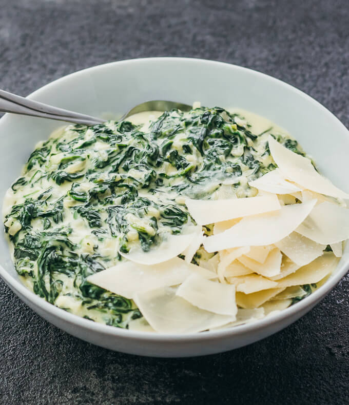 Easy creamed spinach topped with shaved parmesan served in a white bowl