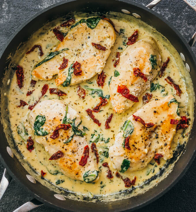 tuscan chicken with sun-dried tomatoes and spinach in a creamy buttery sauce on black pan