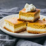 These pumpkin cheesecake bars are layered with a bottom almond crust, a middle cheesecake layer, and a top pumpkin layer. They are low in carbs and perfect as a keto-friendly holiday dessert.