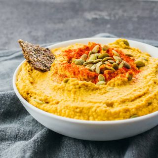 Pumpkin hummus plated in a serving bowl topped with pumpkin seeds, paprika, and flax seed cracker