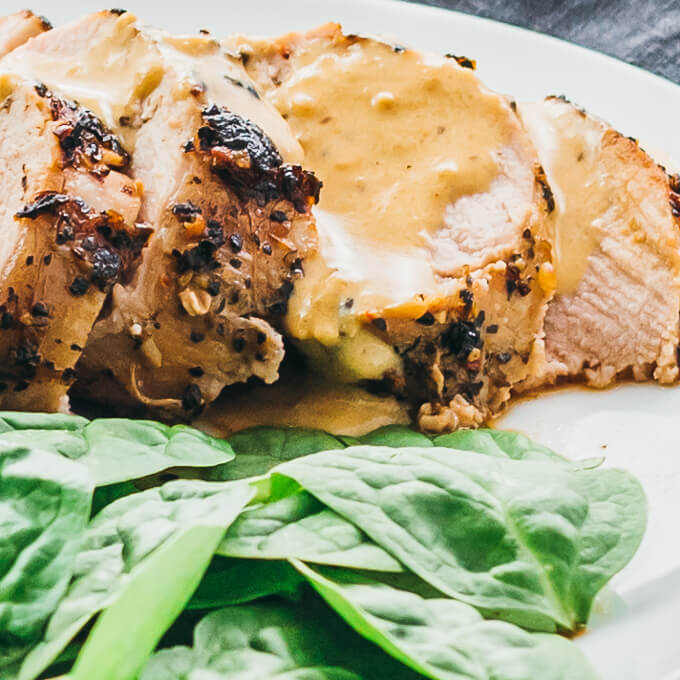Close up view of a creamy mustard sauce on sliced pork tenderloin with spinach