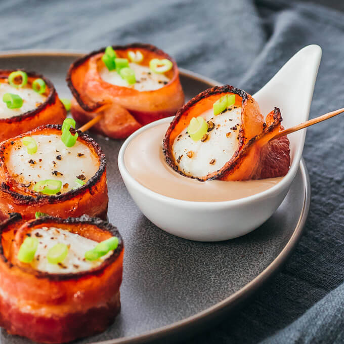 Easy scallops recipe wrapped in bacon being served with balsamic mayo sauce
