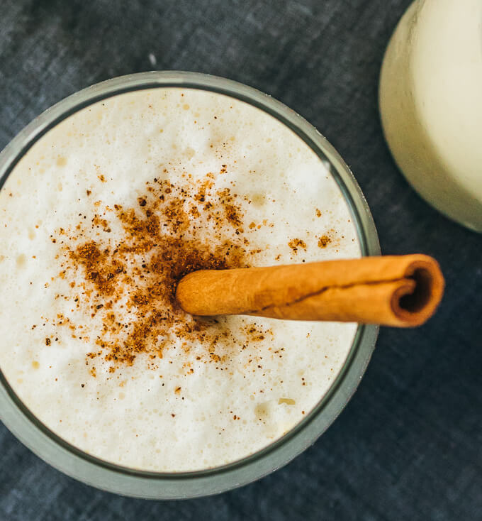 Overhead view of easy and best keto traditional eggnog drink with almond milk, topped with spices and cinnamon stick