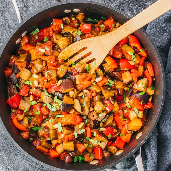 cooking eggplant caponata in black pan