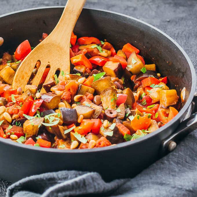 Low carb eggplant caponata recipe being made in a pan with a wooden spoon