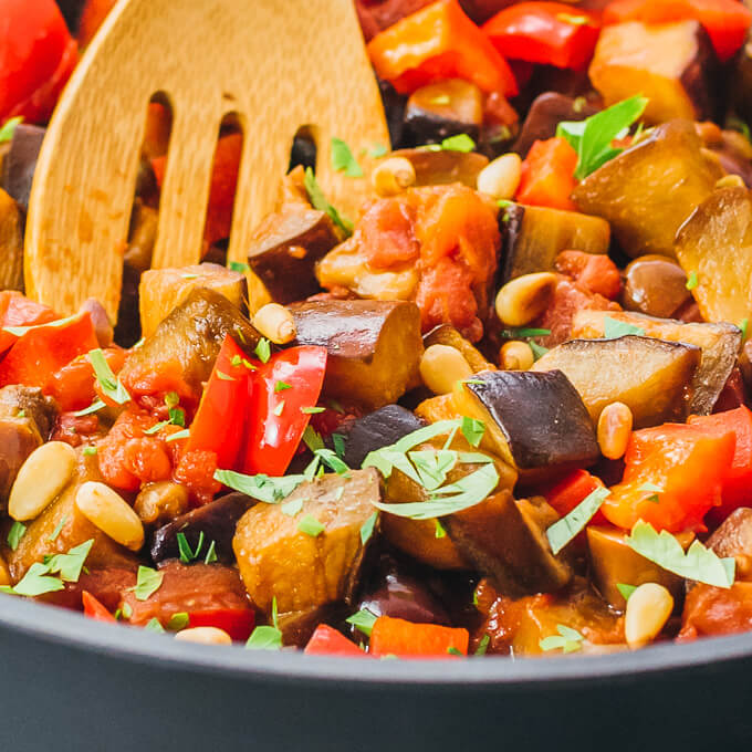 Close up photo of wooden spoon with eggplant caponata recipe