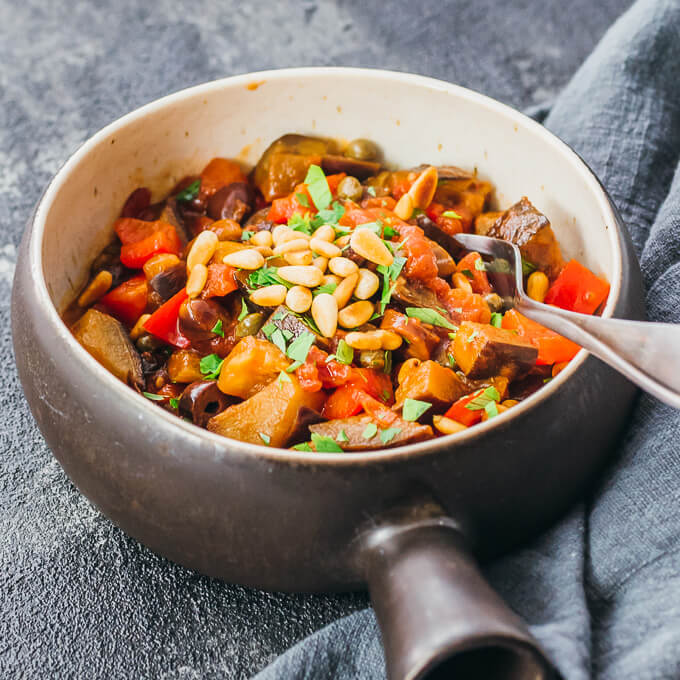 Keto eggplant caponata served in a brown bowl topped with pine nuts and parsley