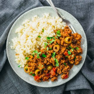 An easy-to-make beef picadillo served with cauliflower rice on a plate