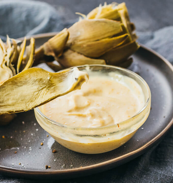 Demonstrating how to dip an artichoke leaf into a spicy garlic mustard sauce