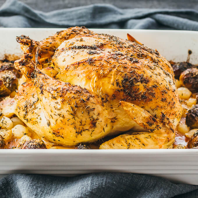 Whole roast chicken cooked with healthy low carb vegetables including brussels sprouts and onions
