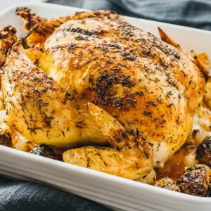 Simple roast chicken baked in casserole pan with vegetables including onions and brussels sprouts