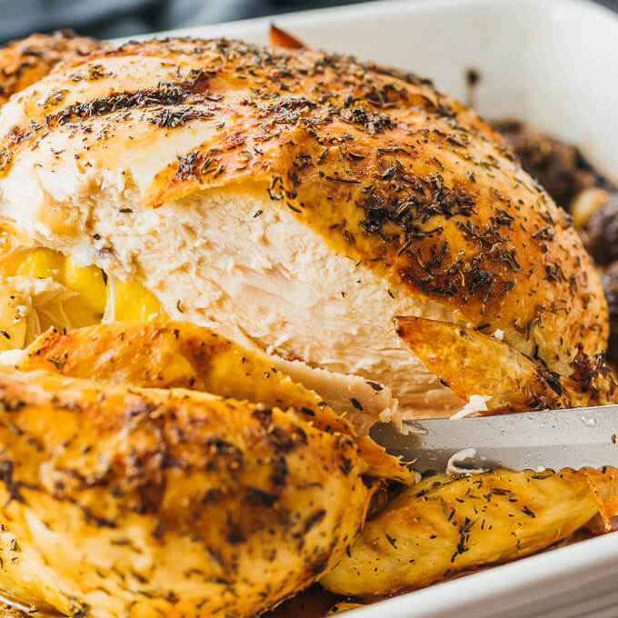 Simple roast chicken being sliced after cooking to reveal juicy tender meat and a crisp skin